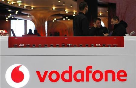 The Vodafone logo is seen at the counter of the shop as customers look at mobile phones in Prague February 7, 2012. REUTERS/David W Cerny/Files