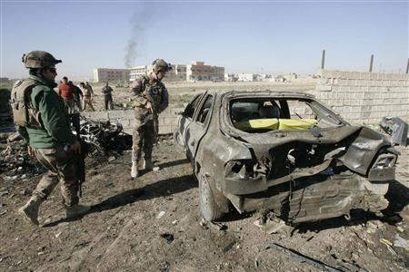 Iraqi security forces inspect the site of a bomb attack in Kirkuk, 250 km (155 miles) north of Baghdad, March 20, 2012. REUTERS/Ako Rasheed