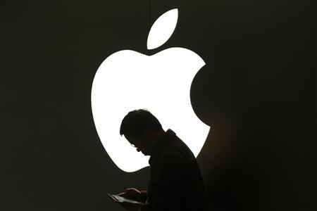 A man looks at his Apple iPad in front an Apple logo outside an Apple store in downtown Shanghai in this March 16, 2012 file photo. REUTERS/Aly Song/Files