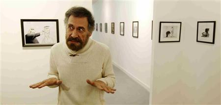 Syrian artist Ali Ferzat reacts during an interview with Reuters alongside his artworks being exhibited at the Mica Gallery in London March 19, 2012. Picture taken March 19, 2012. REUTERS/Luke MacGregor