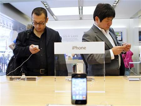 Customers try out the iPhone 4S at the Apple retail store in San Francisco, California November 17, 2011. REUTERS/Robert Galbraith/Files