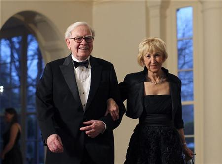 Business magnate Warren Buffett and his wife Astrid Menks arrive for a State Dinner held in honor of Britain's Prime Minister David Cameron and his wife Samantha at the White House in Washington March 14, 2012. REUTERS/Benjamin Myers