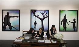Women work at a desk while sitting in front of artwork by artist Andres Serrano during the 2012 Armory Show art fair in New York March 8, 2012. REUTERS/Lucas Jackson