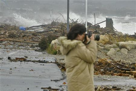 A woman photographs the sea as it pounds the devastated coastline between Nice and Antibes in southern France, November 6, 2011. REUTERS/Jean-Pierre Amet