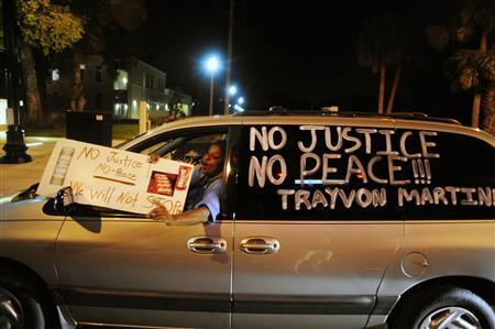 An unidentified driver protests the death of Trayvon Martin outside Sanford Police Headquarters in Sanford, Florida March 20, 2012. REUTERS/David Manning