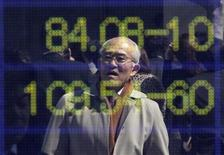 A man is reflected on an electronic board displaying exchange rates in a business district in Tokyo March 15, 2012. REUTERS/Toru Hanai
