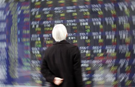 A man looks at a screen displaying stock prices in Tokyo March 16, 2011. REUTERS/Issei Kato/Files