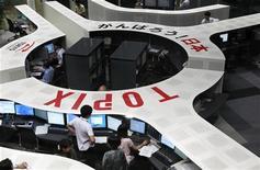 Трейдеры работают в торговом зале Токийской фондовой биржи, 5 августа 2011 года. Азиатские фондовые рынки, кроме Шанхая, снизились в среду, а южнокорейские акции упали до минимальной отметки за неделю, на фоне озабоченности инвесторов замедлением экономического роста Китая. REUTERS/Issei Kato
