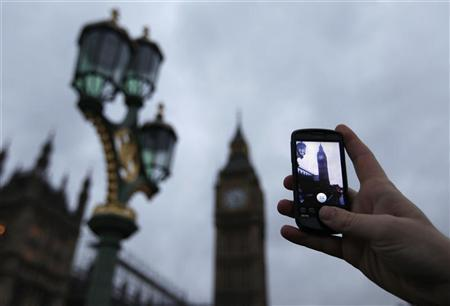 A Google employee holds up a mobile phone to demonstrate how the new Goggles application recognises Big Ben as seen from Westminster Bridge in central London December 7, 2009. REUTERS/Andrew Winning