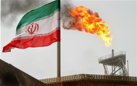 Gas flares from an oil production platform at the Soroush oil fields with an Iranian flag in the foreground in the Persian Gulf, 1,250 km (776 miles) south of the capital Tehran, July 25, 2005. Picture taken July 25, 2005. REUTERS/Raheb Homavandi