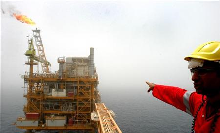 An Iranian man points to an oil production platform at the Soroush oil fields in the Persian Gulf, 1,250 km (776 miles) south of the capital Tehran, July 25, 2005. REUTERS/Raheb Homavandi