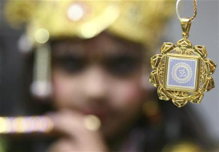 A child dressed as Hindu Lord Krishna poses with a miniature 'Bhagavad-Gita', a scared scripture of Hinduism, in the northern Indian city of Chandigarh May 1, 2009. The Bhagavad-Gita is a part of the Mahabharata, comprising 700 verses as teacher of the Bhagavad-Gita is Krishna, who is regarded by the Hindus as the supreme manifestation of the Lord himself, and is referred to within as Bhagavan - the divine one. REUTERS/Ajay Verma