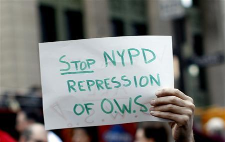 A man holds a sign at a news conference in Zuccotti Park in New York, March 19, 2012, held to denounce what they claim to be brutality by New York City Police (NYPD) during arrests of Occupy Wall Street protestors. REUTERS/Mike Segar