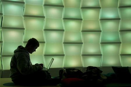 A woman uses a computer in the lounge area of the 27th Chaos Communication Congress (27C3) in Berlin, December 27, 2010. REUTERS/Thomas Peter