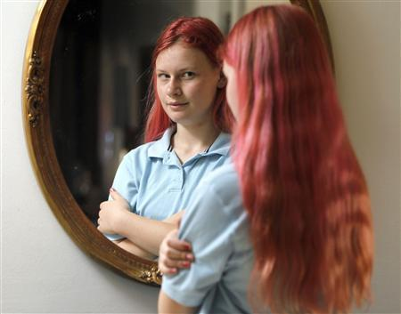 Delaware middle school student Brianna Moore stands in front of the mirror with pink hair at her residence in Newark, Delaware March 20, 2012. Moore was sent home from school for having pink hair that her father helped her dye after she improved her grades. REUTERS/Tim Shaffer