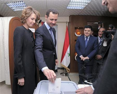 Syria's President Bashar al-Assad and his wife Asma vote during a referendum on a new constitution at a polling station in a Syrian TV station building in Damascus February 26, 2012, in this handout photograph released by Syria's national news agency SANA. REUTERS/SANA