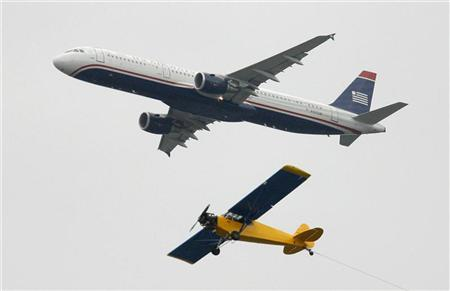 A US Airways Airbus A321 passenger jet flies past a propeller airplane pulling a banner before the start of the Washington Redskins versus Philadelphia Eagles NFL football game in Philadelphia, Pennsylvania, October 3, 2010. REUTERS/Tim Shaffer