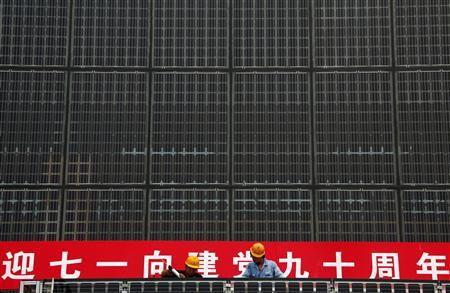 Workers stand atop scaffolding as they work on a building covered with solar panels, located near the factory of the Yingli Green Energy Holding Company, also known as Yingli Solar, in the city of Baoding, Hebei Province, in this June 20, 2011 file picture. REUTERS/David Gray/Files