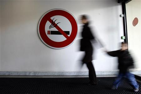 A woman walks past a ''No Smoking'' sign in Nice, southeastern France, February 12, 2007. REUTERS/Eric Gaillard