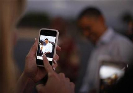 A woman takes a picture of U.S. President Barack Obama with her iPhone upon his arrival at Hickam Air Base near Honolulu, Hawaii, December 23, 2011. REUTERS/Jason Reed