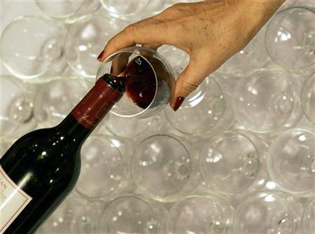 A woman tastes red wine in the Millesima cellar in Bordeaux, southwestern France, November 6, 2007. REUTERS/Regis Duvignau