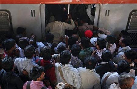 Commuters try to get onto an overcrowded train on a railway platform during the morning rush hour in Mumbai March 14, 2012. REUTERS/Danish Siddiqui