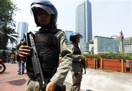Indonesian anti-terror policemen hold their rifle as they stand guard at the business district in Jakarta, September 11, 2011. REUTERS/Beawiharta