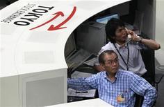 Трейдеры следят за торгами на бирже в Токио, 5 августа 2011 года. Фондовые рынки Азии закрылись разнонаправлено: индексы Японии и Гонконга выросли, а Южной Кореи и Китая - снизились. REUTERS/Issei Kato