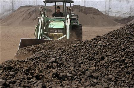 A worker uses a loader to assemble the coal at a yard in Ahmedabad March 22, 2012. REUTERS/Amit Dave