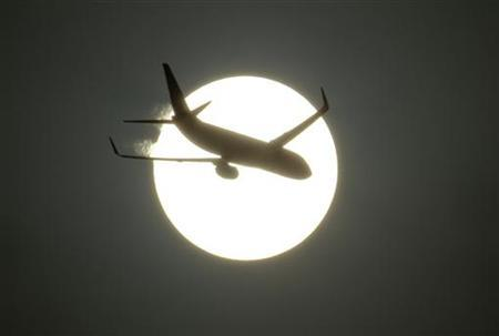 An aircraft is silhouetted by the sun in New Delhi June 13, 2011. REUTERS/B Mathur