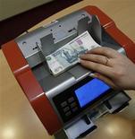 Кассир считает деньги в банке в Санкт-Петербурге, 4 февраля 2011 года. Рубль в минусе к бивалютной корзине на дневных торгах четверга, реагируя на снижение интереса к рискованным активам и падение нефтяных цен после данных о замедлении деловой активности в Китае и странах Еврозоны, подешевел к валюте США и отбил убыток в паре с единой европейской валютой в ответ на падение пары евро/доллар. REUTERS/Alexander Demianchuk