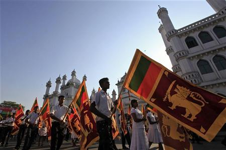 Sri Lankans hold Sri Lankan national flags as they march during a ceremony to pray for the defeat of a U.N. resolution calling on Sri Lanka to probe wartime human rights abuses in Colombo March 19, 2012. REUTERS/Stringer