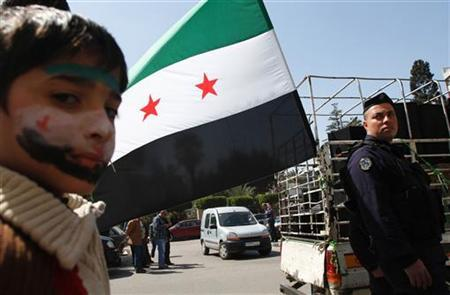 A Syrian boy who recently fled from Syria displays a drawing of the Syrian opposition flag on his face during a demonstration in celebration of mother's day and in solidarity with Syrian mothers against the Syrian regime, in Tripoli, northern Lebanon March 21, 2012. REUTERS/Omar Ibrahim