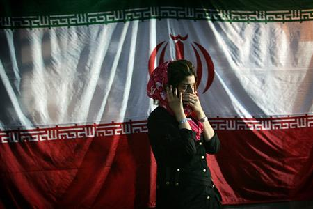 An Iranian girl talks on her mobile phone in front of the national flag at a campaign centre in Tehran June 6, 2005. REUTERS/Damir Sagolj/Files
