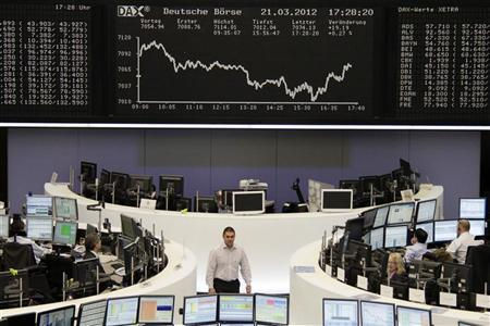 Traders are pictured at their desks in front of the DAX board at the Frankfurt stock exchange March 21, 2012. REUTERS/Remote/Antonio Bronic