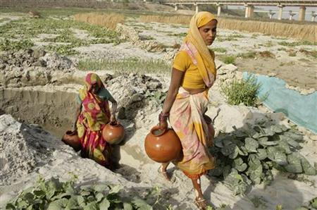 Women carry earthen pitchers after filling them with water from a pit on the river bank of the Ganges in Allahabad March 22, 2012. REUTERS/Jitendra Prakash