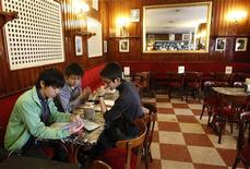 Tourists sit inside Spain's historic Cafe Gijon in Madrid March 16, 2012. Staff of the Cafe Gijon face uncertainty as Madrid City Hall has put the establishment's money-making terrace up for bids. Cafe Gijon has been home to Spain's intellectuals and artists for 124 years, but staff fear without the terrace the cafe could close. Picture taken on March 16, 2012. REUTERS/Andrea Comas
