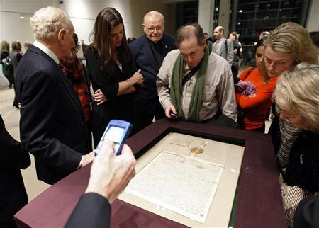 People look at a 1297 copy of the Magna Carta after it was sold at Sotheby's auction house for $21,321,000 in New York December 18, 2007. The Magna Carta is known as the basis of many parts of current law, most notably, the writ of habeas corpus, which allows appeal by prisoners against unlawful imprisonment by government. REUTERS/Chip East