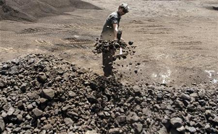 A worker shovels coal at a yard in Ahmedabad March 22, 2012. REUTERS/Amit Dave