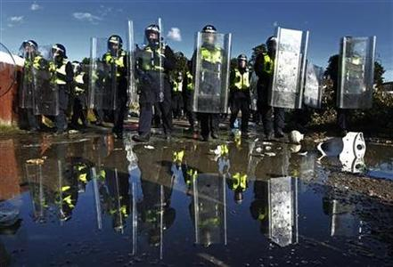 Police officers walk ahead of council officials as they inspect the Dale Farm travellers' site, near Billericay in southern England October 20, 2011. A REUTERS/Luke MacGregor