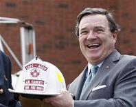Canada's Finance Minister Jim Flaherty reacts as he receives a firefighter's helmet during a news conference at Fire Station 81 in Stittsville, Ontario March 22, 2012. REUTERS/Chris Wattie