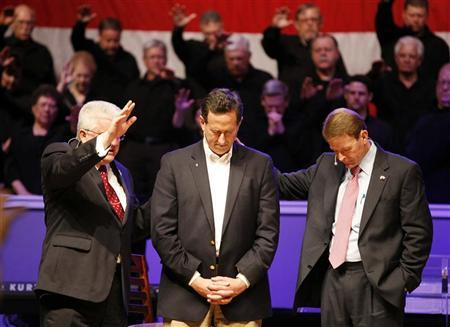 Republican presidential candidate and former U.S. Senator Rick Santorum (C) receives a blessing from Pastor Dennis E. Terry, Sr. (L) after being interviewed by Family Research Council President Tony Perkins (R) at Greenwell Springs Baptist Church in Greenwell Springs, Louisiana March 18, 2012. REUTERS/Sean Gardner