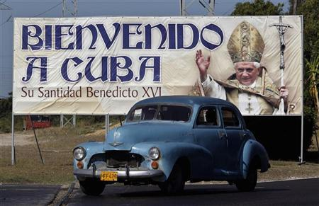 A car drives past a poster of Pope Benedict XVI, which reads ''welcome to Cuba'' in Havana March 21, 2012. Pope Benedict will visit Cuba on March 26-28. REUTERS/Enrique de la Osa