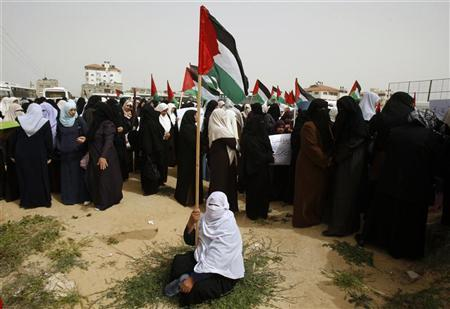 A Palestinian woman holds a flag during a rally calling on Egyptian authorities to supply the Gaza Strip with fuel and electricity, in Rafah, on the border between Egypt and the southern Gaza Strip March 20, 2012. REUTERS/Ibraheem Abu Mustafa
