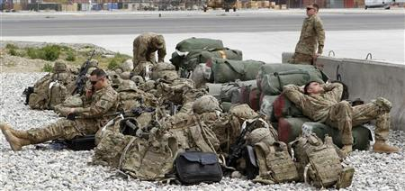 U.S. army soldiers of 3rd Brigade, 25th Infantry rest among luggage while waiting for a flight to go home to the United States after finishing their one-year deployment in Afghanistan, at Forward Operating Base Fenty in Jalalabad, eastern Afghanistan March 23, 2012. REUTERS/Erik De Castro
