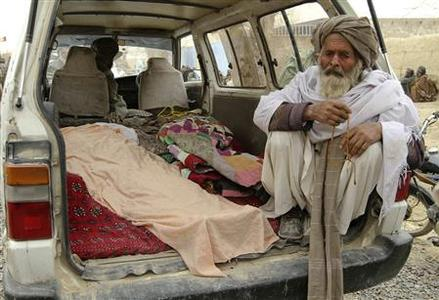 An Afghan man sits next to the covered bodies of people who were killed by coalition forces in Kandahar province in this March 11, 2012 file photo. Army Staff Sergeant Robert Bales, accused of killing Afghan civilians in a shooting rampage in Kandahar province last week, will be charged with 17 counts of murder, a U.S. official said on March 22, 2012. REUTERS/Ahmad Nadeem/Files (AFGHANISTAN - Tags: CRIME LAW POLITICS MILITARY)
