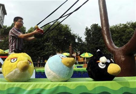 A visitor uses a slingshot to shoot an Angry Bird plush toy at a real life Angry Birds outdoor game in a theme park at Changsha, Hunan province September 1, 2011. REUTERS/China Daily/Files