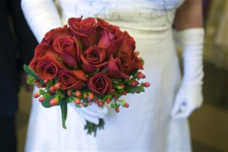 Lorie Lesieur of Pawtucket, Rhode Island, holds a bouquet after being married in The Mob Museum in Las Vegas, Nevada February 14, 2012. REUTERS/Steve Marcus/Files
