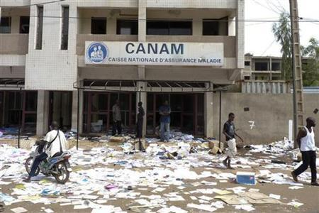 People wander through the wreckage of an insurance company office looted after the Malian army staged a coup, in the capital Bamako, March 23, 2012. REUTERS/Adama Diarra