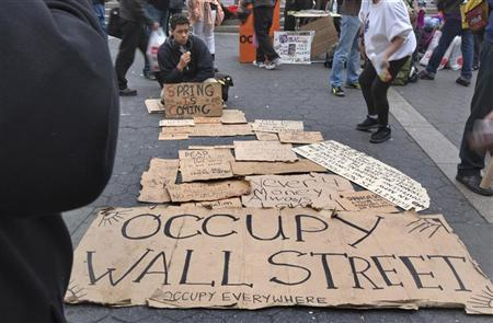 An Occupy Wall Street protester sits near makeshift signs in New York's Union Square March 21, 2012. REUTERS/Adrees Latif
